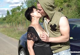 Perverted short haired mature brunette stands on knees to give BJ into the open air